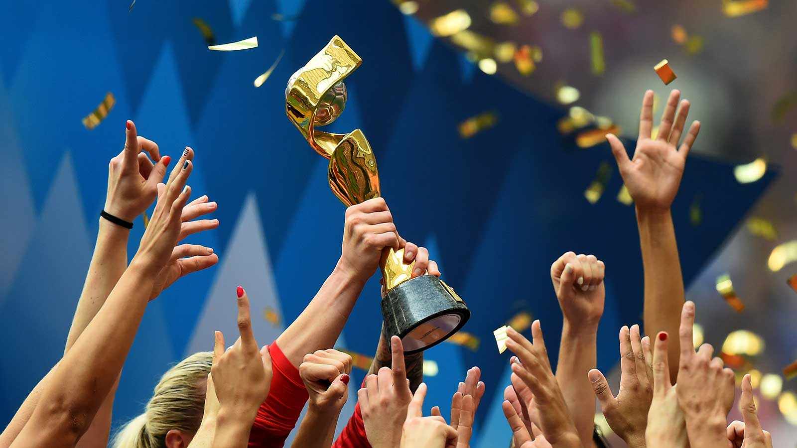 Women's world cup trophy being held up in the air